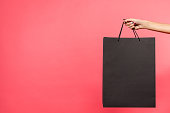 istock woman holding black shopping bag 901571470