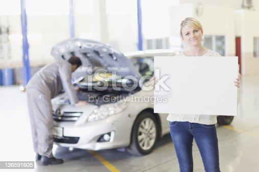 136591855 istock photo Woman holding blank card in garage 136591605