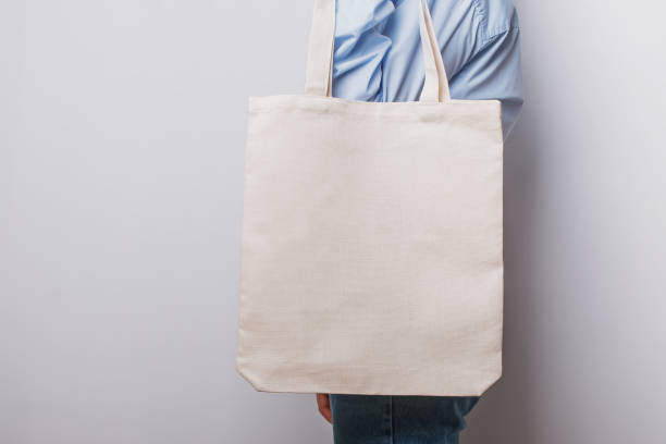 Woman holding blank cotton eco tote bag stock photo