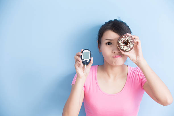 woman holding  blood glucose meter Woman holding a blood glucose meter and donut to prevention diabetes isolated on blue background, asian hypoglycemia stock pictures, royalty-free photos & images