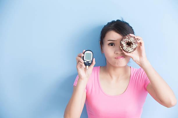 woman holding  blood glucose meter - hypoglykämie stock-fotos und bilder