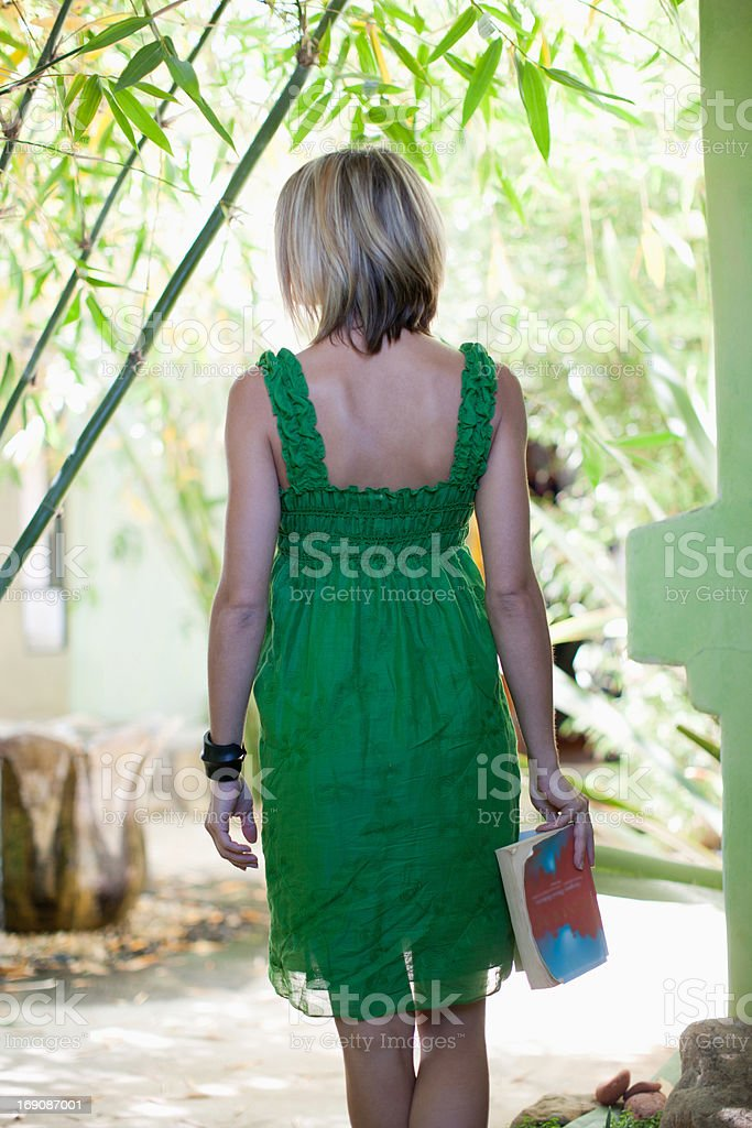 Woman holding book on patio royalty-free stock photo