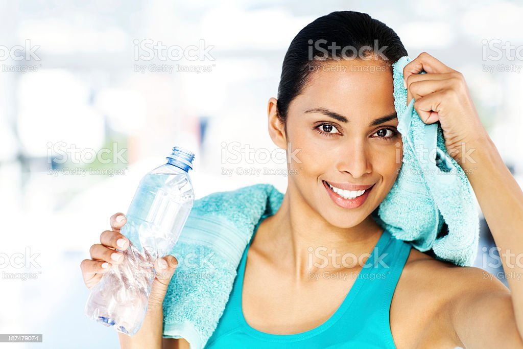 Woman Holding Bottle While Cleaning Sweat From Forehead In Gym stock photo