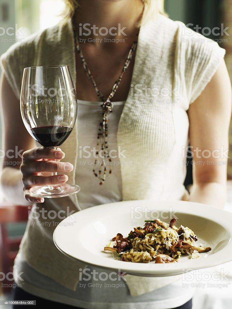 Woman holding bowl of chanterelle risotto and glass of red wine, mid section, close-up royalty free stockfoto