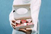 Woman holding box with Valentine's cookies in heart forms