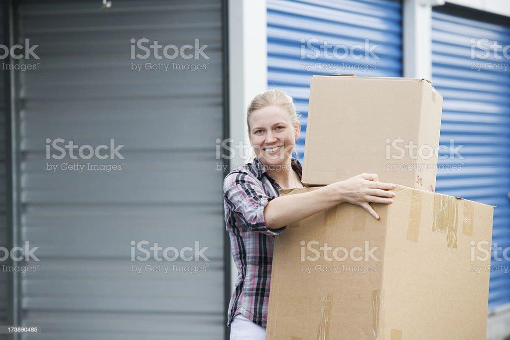 Woman Holding Boxes Outside Self Storage Unit stock photo