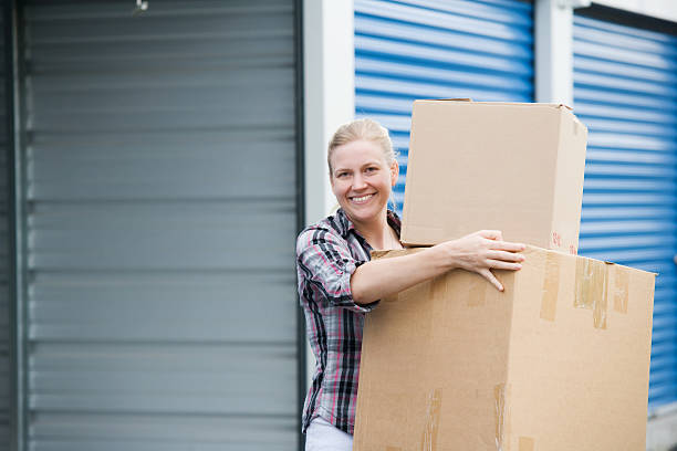 Woman Holding Boxes Outside Self Storage Unit stock photo