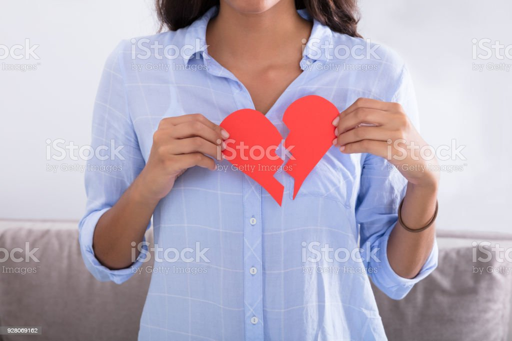 Woman Holding Broken Red Valentine Paper Heart stock photo
