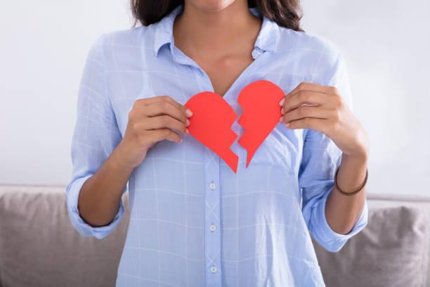 vrouw met rode valentine papier hart gebroken - liefdesverdriet stockfoto's en -beelden