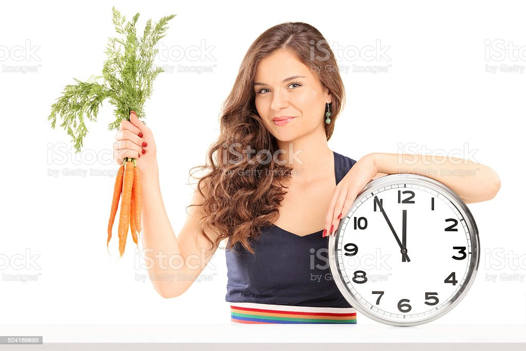 Woman holding bunch of carrots and a big wall clock stock photo