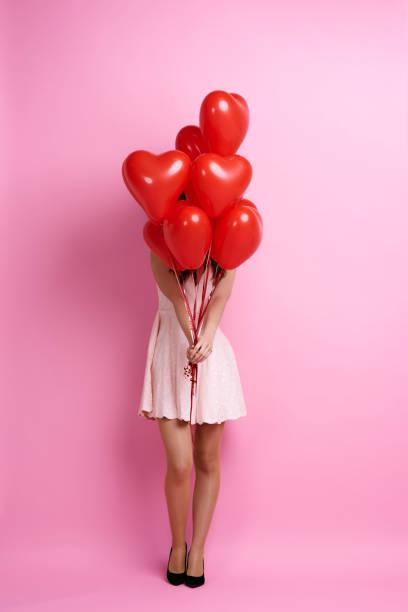 woman holding bunch of heart shape balloons - mulher balões imagens e fotografias de stock