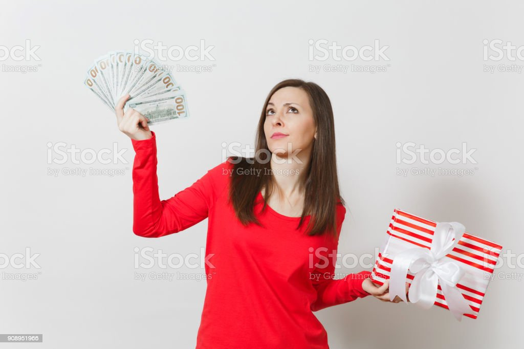Woman holding bundle cash money dollars, red present box with gift isolated on white background. For advertisement. St. Valentine's Day, International Women's Day, Christmas, birthday, holiday concept stock photo