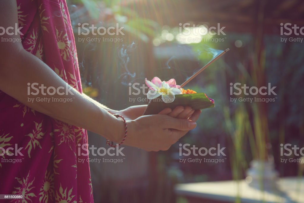 Woman holding canang sari - offering for Gods. Balinese tradition. stock photo