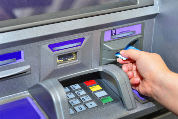 Woman holding card ,using ATM Woman using her credit card on ATM machine banks and atms stock pictures, royalty-free photos & images