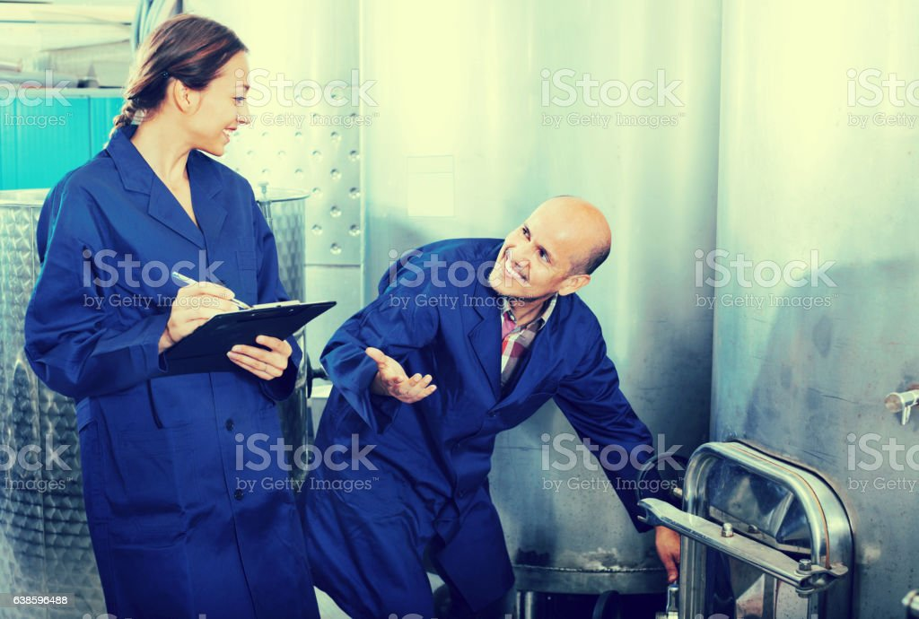 Woman holding cardboard and standing with man working stock photo