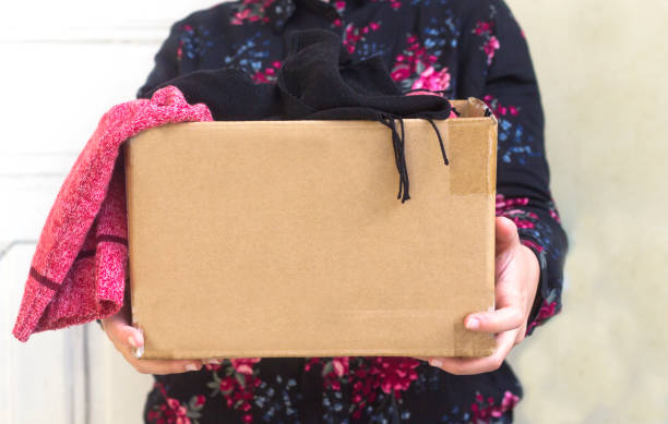 woman holding cardboard box with clothing during clothing drive stock photo