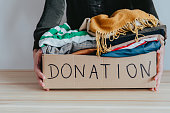 istock Woman holding cardboard donation box full with folded clothes. 1283154274