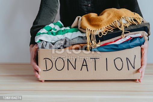 Woman holding cardboard donation box full with clothes. Concept of volunteering work, donation and clothes recycling. Helping poor people
