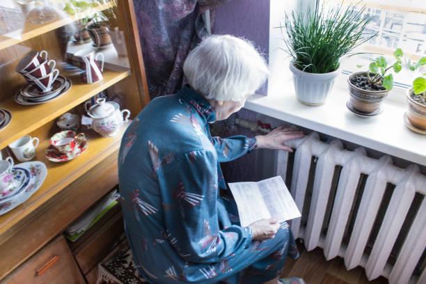 Frau Bargeldhaltung vor Heizung Heizkörper. Zahlung für Heizung im Winter. Selektiven Fokus. – Foto