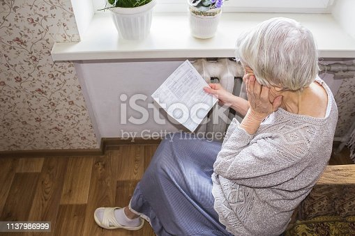 istock Woman holding cash in front of heating radiator. Payment for heating in winter. Selective focus. 1137986999