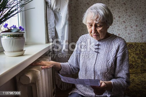 istock Woman holding cash in front of heating radiator. Payment for heating in winter. Selective focus. 1137987005
