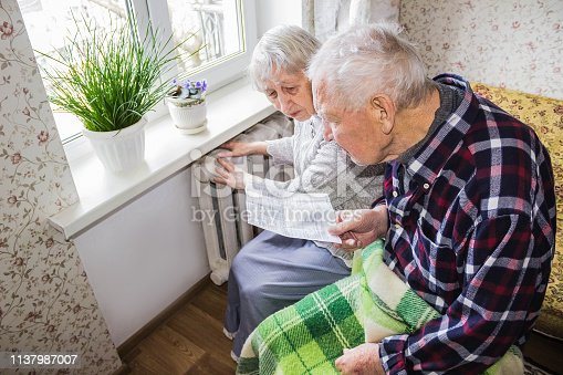 istock Woman holding cash in front of heating radiator. Payment for heating in winter. Selective focus. 1137987007