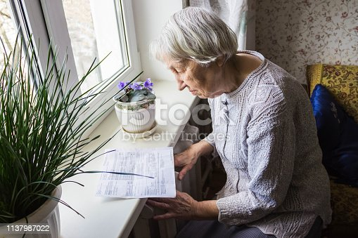 istock Woman holding cash in front of heating radiator. Payment for heating in winter. Selective focus. 1137987022