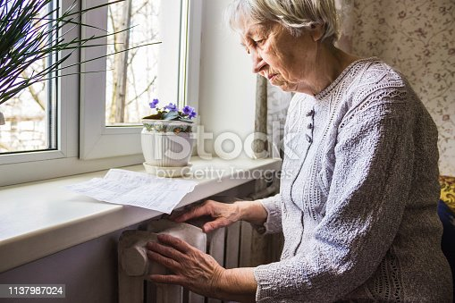 istock Woman holding cash in front of heating radiator. Payment for heating in winter. Selective focus. 1137987024