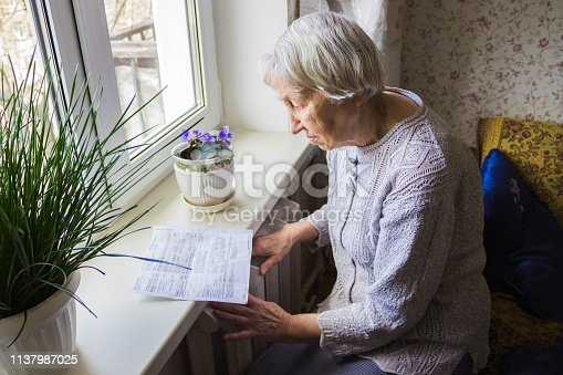 istock Woman holding cash in front of heating radiator. Payment for heating in winter. Selective focus. 1137987025