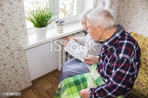 istock Woman holding cash in front of heating radiator. Payment for heating in winter. Selective focus. 1137987027