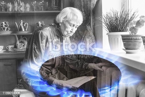 istock Woman holding cash in front of heating radiator. Payment for heating in winter. 1159010006