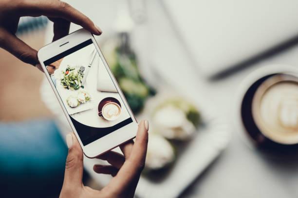frau, zellulärer in händen und unter bild von ihr zu essen - fotografische themen stock-fotos und bilder