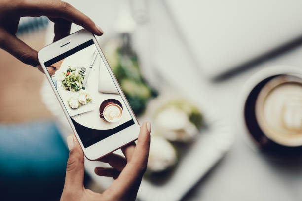 Woman holding cellular in hands and taking picture of her food stock photo