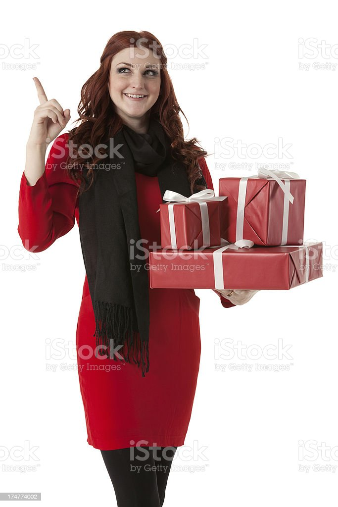 Woman holding Christmas presents and pointing royalty-free stock photo