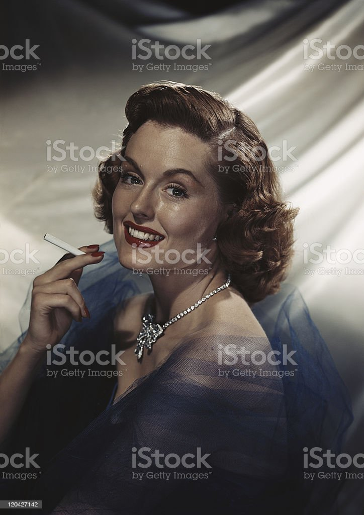 Woman holding cigarette, smiling, portrait stock photo