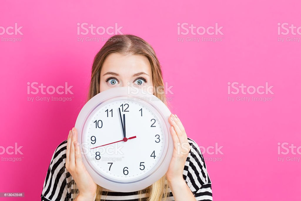 Woman holding clock showing nearly 12 – Foto