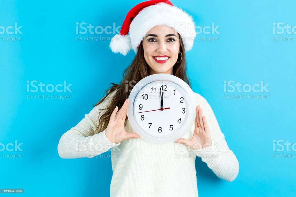 Woman holding clock showing nearly 12 foto royalty-free