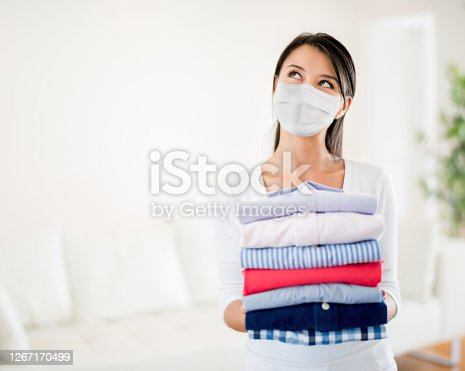 Portrait of a Latin American woman holding clothes after doing the laundry and wearing a facemask – COVID-19 pandemic lifestyle