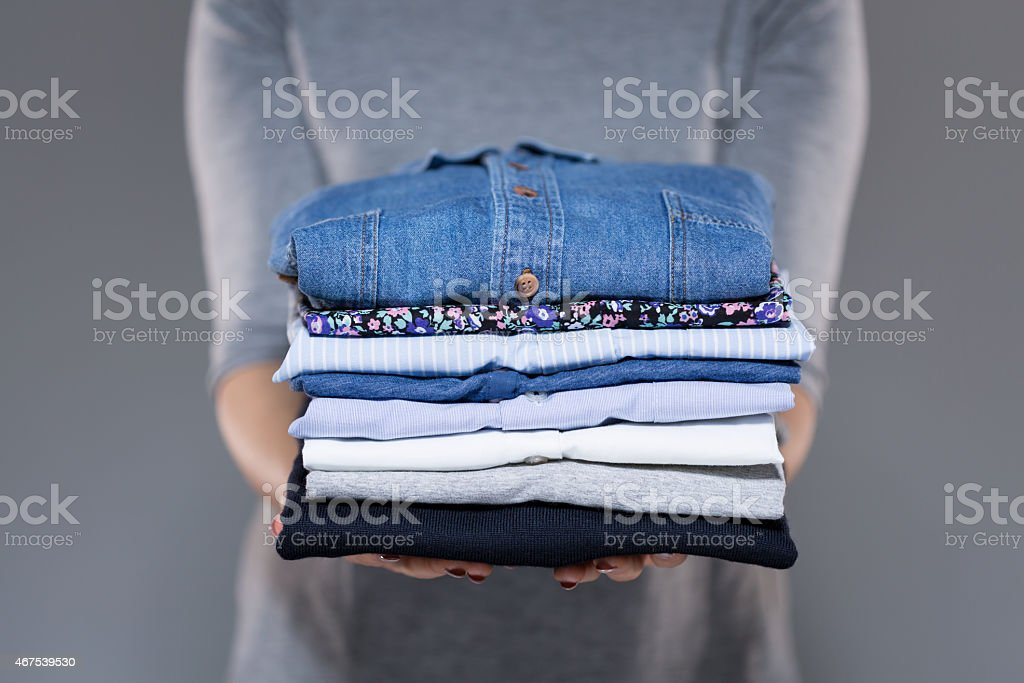 Woman holding clothes in hands stock photo