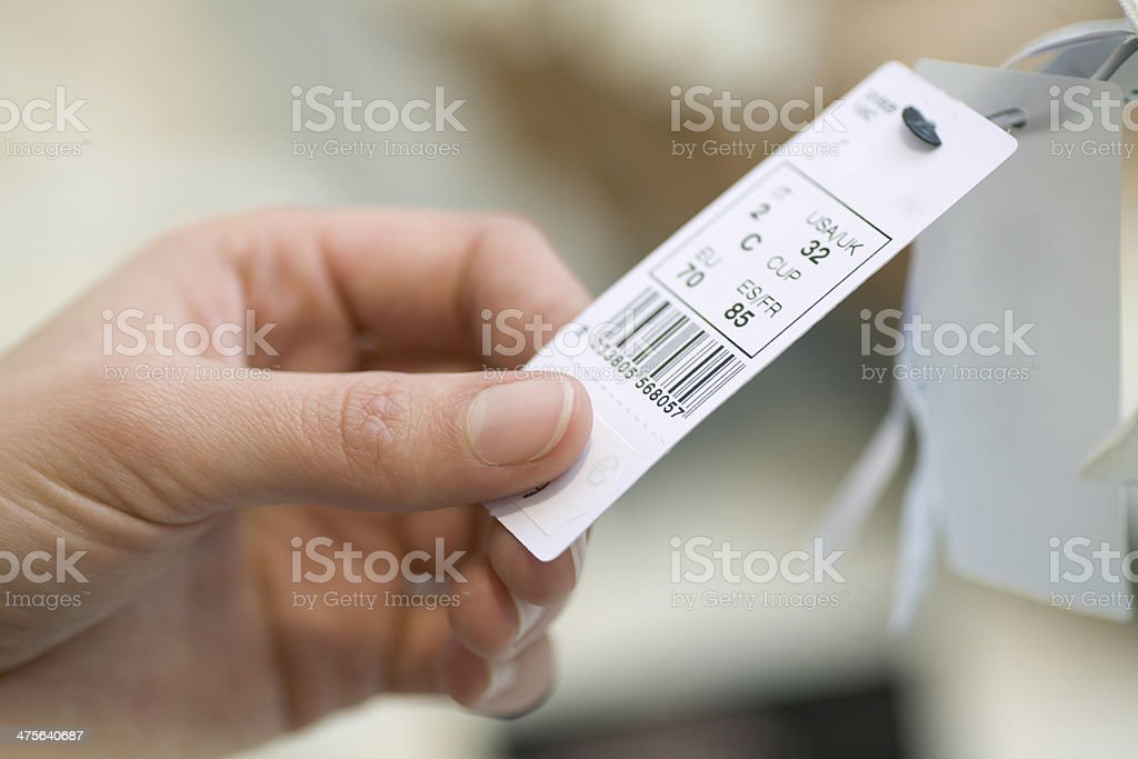 Woman Holding Clothes Tag In Store stock photo