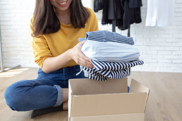 Woman holding Clothes with Donate Box In her room, Donation Concept. Woman holding Clothes with Donate Box In her room, Donation Concept. clothes in box stock pictures, royalty-free photos & images