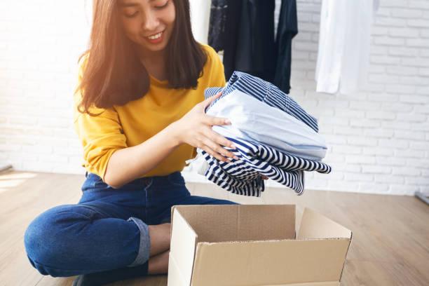 kobieta trzymająca ubrania z darem box w swoim pokoju, darowizna concept. - odzież zdjęcia i obrazy z banku zdjęć