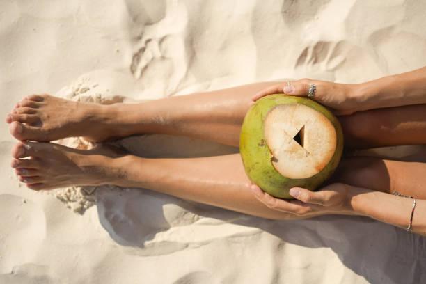 Frau hält Kokosnuss am tropischen Strand – Foto