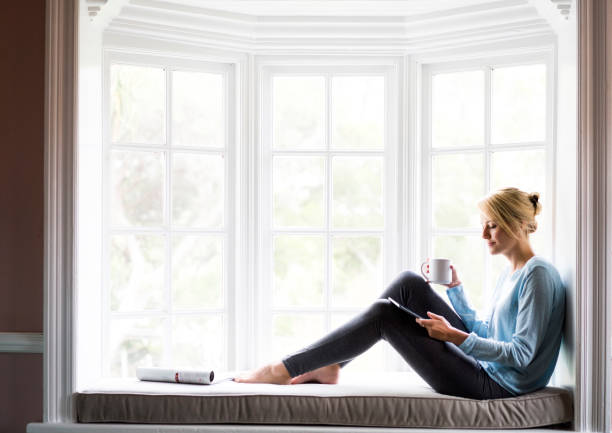 Woman holding coffee and digital tablet by window stock photo