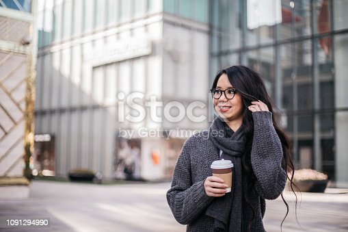 One woman, holding coffee to go on the street downtown.