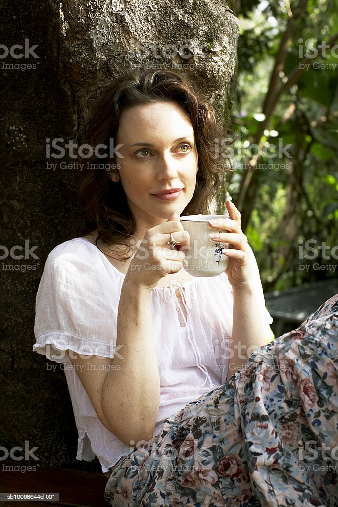 Woman holding coffee cup, smiling royalty free stockfoto