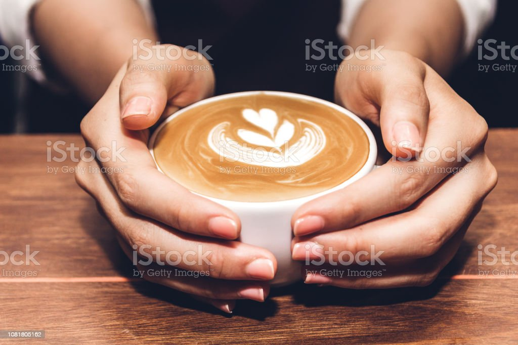 Woman holding coffee latte art on wooden table in coffee shop