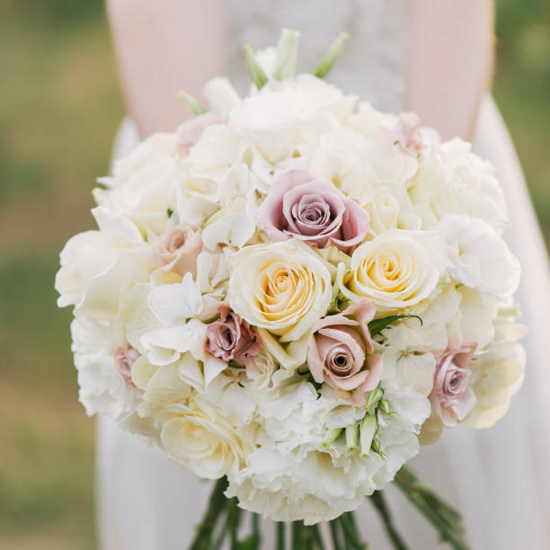 Woman holding colorful bouquet with her hands on wedding day. stock photo