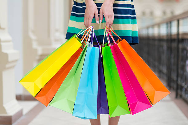 Coloridas mujer sosteniendo bolsas de compras en el centro comercial. - foto de stock