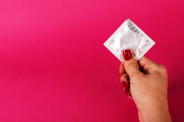 Woman holding condom on the pink background. Sex protection concept